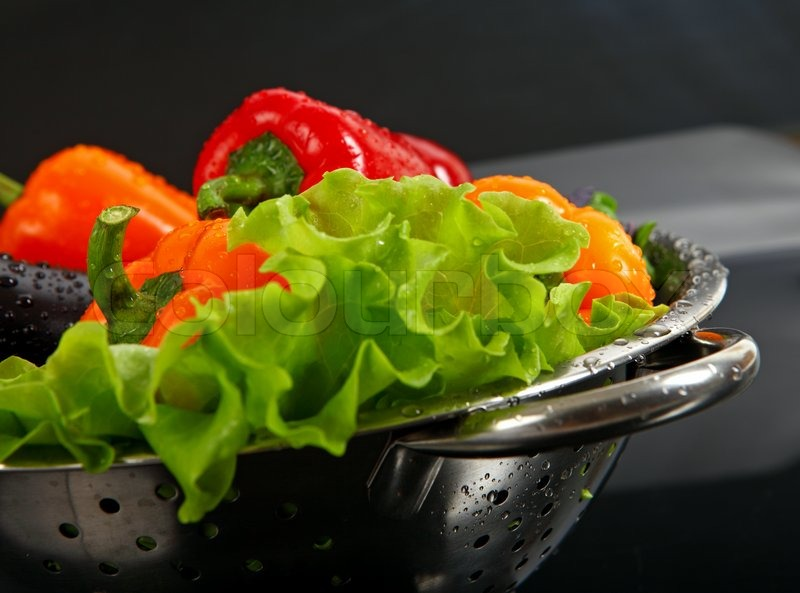 7857187-freshly-washed-fresh-vegetables-in-a-metal-colander-isolated-over-black-background